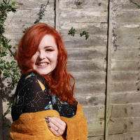 Lucy Edwards smiles at the camera as she wears a black top and holds an amber-colored shawl.