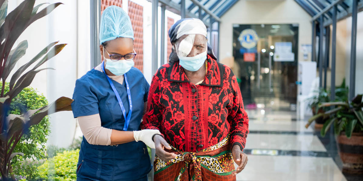 A nurse helps a cataract patient after surgery.